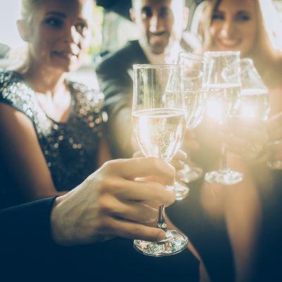 Leende människor skålar i champagne