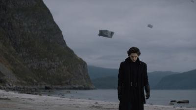Timothée Chalamet i svart slängkappa på en öde strand.
