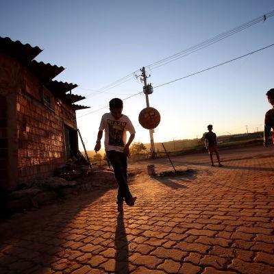 Barn spelar boll.