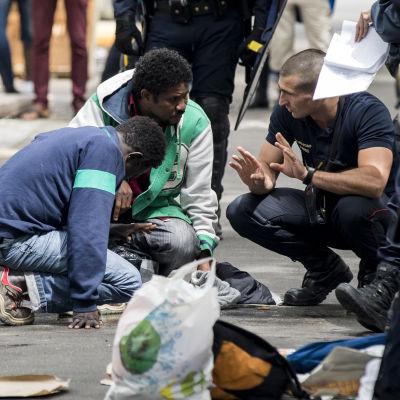 En mgirant tas om hand av brandkår efter att han svimmade när kravallpolis sköt tårgas mot det provisoriska lägret där främst sudaneser och eritreaner bodde i norra Paris i augusti.