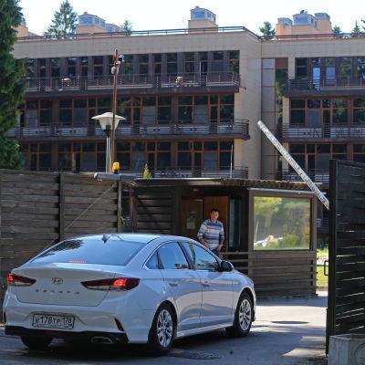 En bil kör in på spelarhotellet gård.