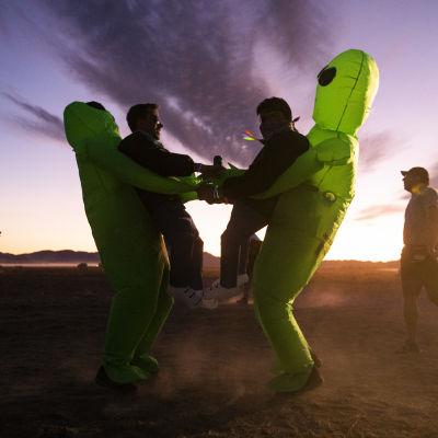 Två personer utklädda till rymdvarelser dansar i soluppgången i byn Rachel utanför Area 51.