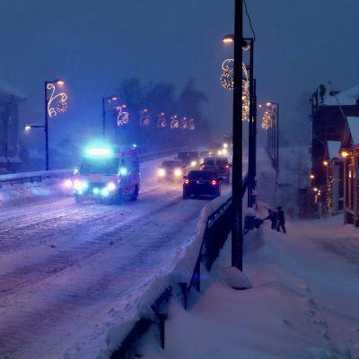 En ambulans kör över Mannerheimgatans bro i Borgå. Det är mörkt och mycket snö på marken.