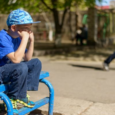 Ledsen pojke sitter ensam på en bänk.