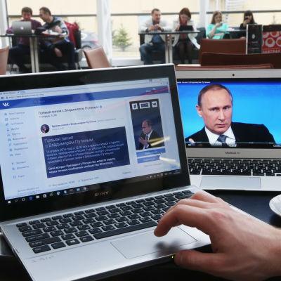 En kaffekopp och två bärbara datorer och på ett bord, på den ena skärmen syns Rysslands president Vladimir Putin och på den andra det populära ryska sociala nätverket en VKontakte.
