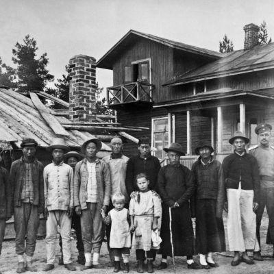 Linnoitustyöt Suomessa ensimmäisen maailmansodan aikana. Kiinalaisia linnoittajia, venäläinen sotilas ja kaksi suomalaista lasta. Ryhmäkuva.