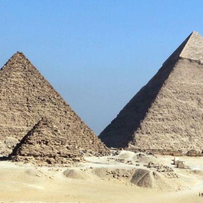Kolme isoa ja kolme pientä pyramidia hiekka-aavikolla.