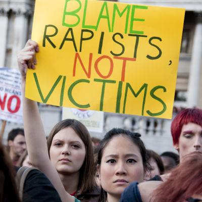 Kvinna som håller upp skylt där det står: Skyll på våldtäktsmännen, inte på offren.