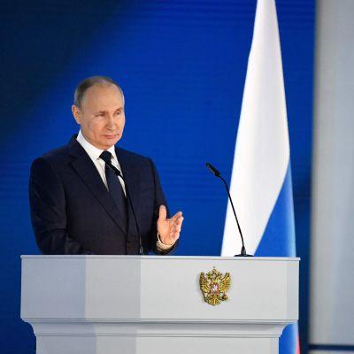 Man i mörk kostym och slips mot en blå bakgrund. Vladimir Putin står bakom en talarstol under sitt tal till nationen den 21 april 2021.