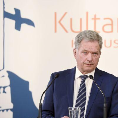Sauli Niinistö på presskonferens, framför logo för Gullrandasamtalen