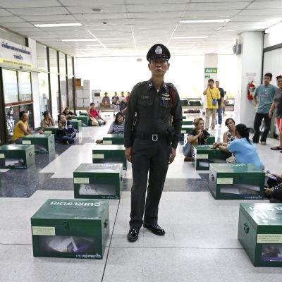 En polis övervakar förberedelserna i en vallokal i Thailand.