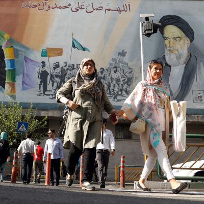 Iranier passerar en väggmålning med iranska martyrer och andliga ledare. Bilden tagen den 22 juli 2018 i Teheran.