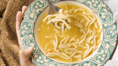 Person inbäddad i filt sitter med en tallrik soppa i famnen