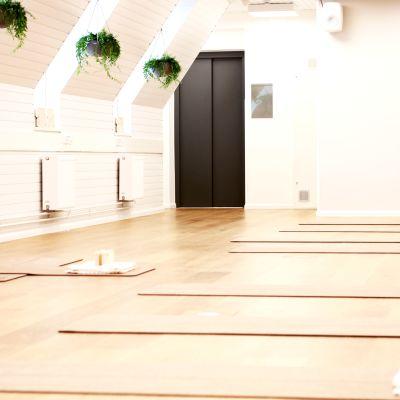En ljus sal med vita väggar, på golvet finns yogamattor och träblock.