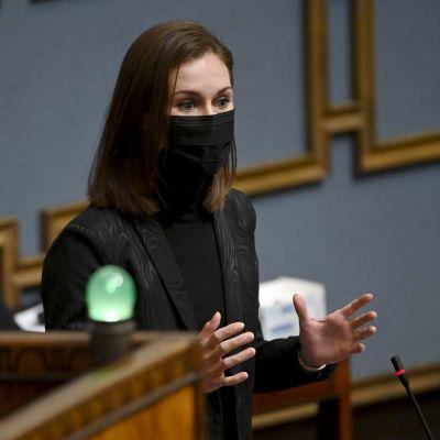 Sanna Marin med svart munskydd talar i riksdagen.