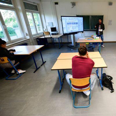 Tre elever och deras lärare med gott om skyddsutrymme, i skola i Dortmund.