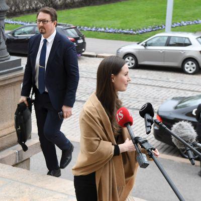 Statsminister Sanna Marin står framför journalisternas mikrofoner på Ständerhusets trappa och i bakgrunden syns Mika Salminen från THL.