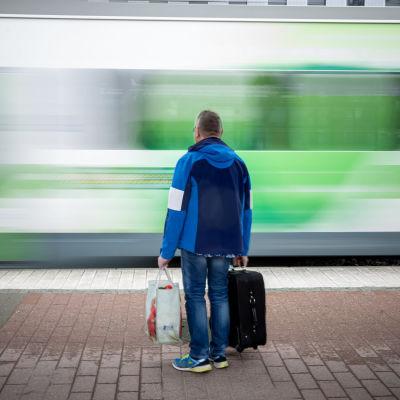 En man väntar på ett tåg på perrongen, samtidigt som ett annat tåg susar förbi.