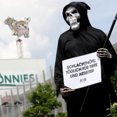 En person utklädd till liemannen utanför Tönnies slakterihögkvarter.