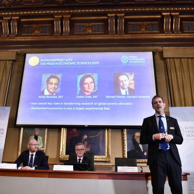 Bild från presskonferensen med fotoporträtt på de tre mottagarna i bakgrunden.