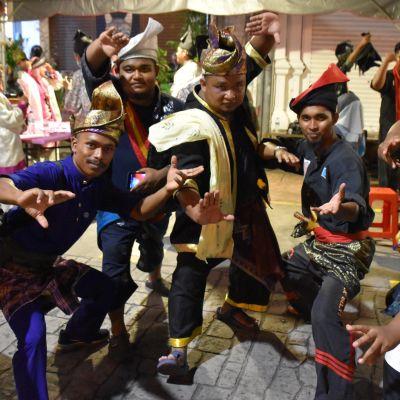 En grupp festklädda malaysiska män tittar mot kameran och intar olika kampställningar.