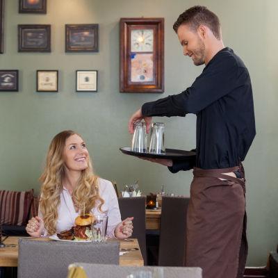 Servitör och kunder i en restaurang.