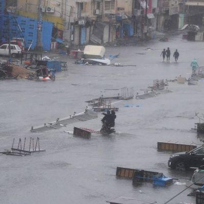 Efter att stormen bedarrat vadade människor fram längs en översvämmad gata i staden Puri, i delstaten Odisha.
