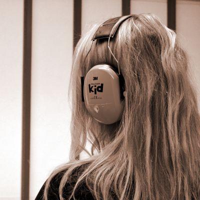 Nainen seisoo kuulosuojaimet päässä.