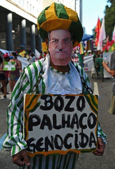 Demonstrant iförd i pappersmask med Jair Bolsonaros ansikte.