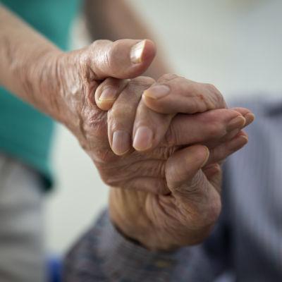 Två äldre som håller varandra i hand. Händerna visas i närbild.