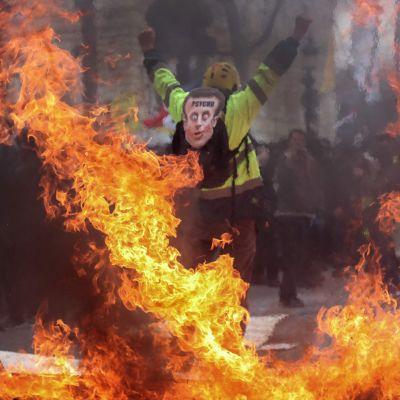 En demonstrant med en Macron-mask bland brinnande barrikader på Champs-Élysées.