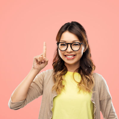 En ung kvinna med glasögon håller upp sitt ena pekfinger.