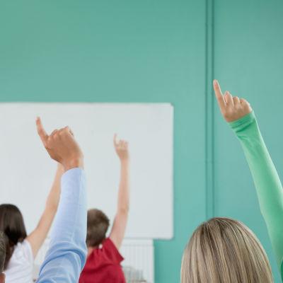 Studerande som markerar i ett klassrum.