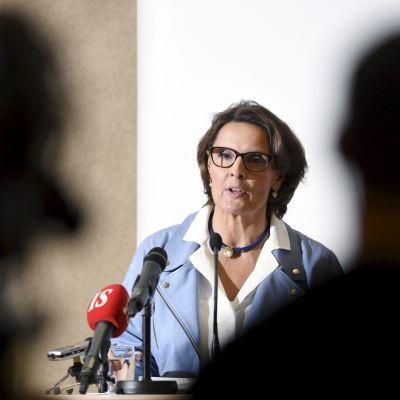 Anne Berner framför publik och mikrofoner på presskonferensen.