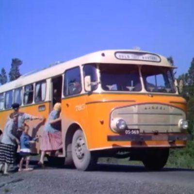 Postiauto kerää matkusatajia kyytiin 60-luvulla.