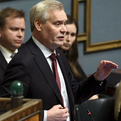 Antti Rinne står med höjd hand på riksdagens frågetimme.