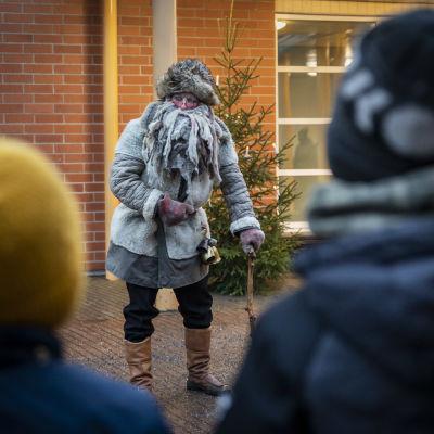 Harmaa pukki esiintyy lapsille koulun pihalla.