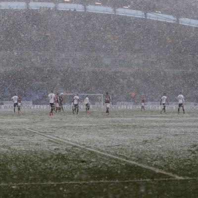 Det snöar under en fotbollsmatch.