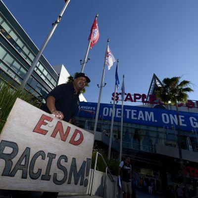 Rasismin vastaista kylttiä pitelevä fani ennen Los Angeles Clippersin ja Golden State Warriorsin välistä NBA-ottelua.