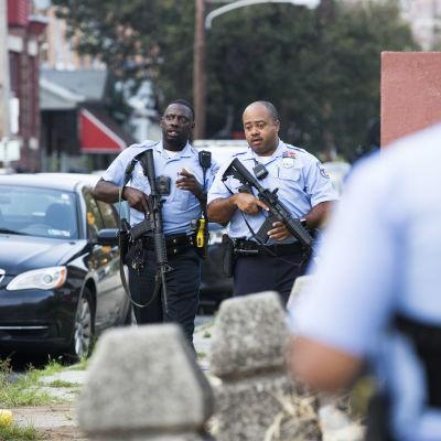 Två poliser med automatgevär går på gatan.