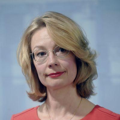 Ministeer Tytti Tuppurainen med glasögon mot en ljusblå vägg.