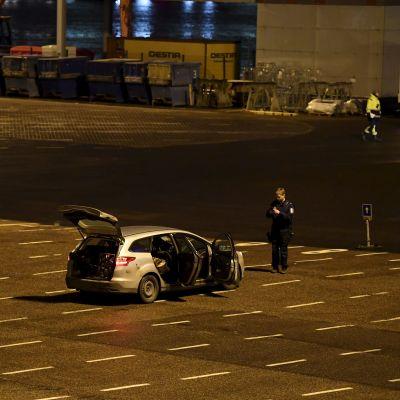 Polisbilar parkerade vid Olympiaterminalen i Helsingfors. En polis står bredvid en bil med öppna dörrar och öppen baggagelucka.
