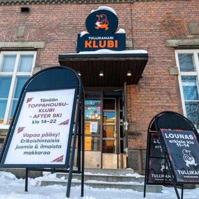 Tampereen Tullikamarin Klubin julkisivu ja Toppahousuklubi -tapahtumasta kertova kyltti