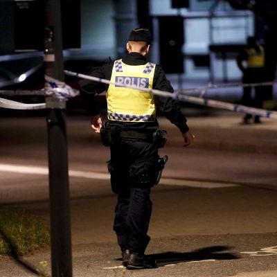 En svensk polis har ryggen mot kameran och står inför ett avstängt område i Göteborg efter en dödsskjutning i juli 2021.