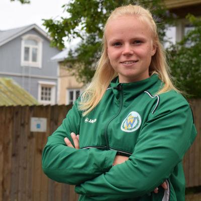 """En ung kvinna med grön klubbjacka med ett """"w"""" på bröstfickan. Bokstaven symboliserar Wågen, en kanotklubb i Ekenäs."""