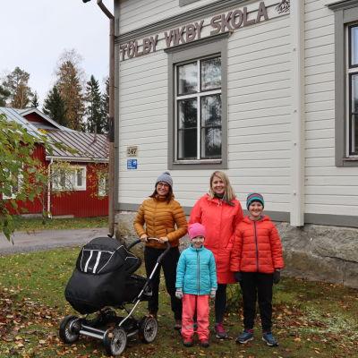 Två kvinnor, ena med barnvagn, och två barn står framför en skolbyggnad.