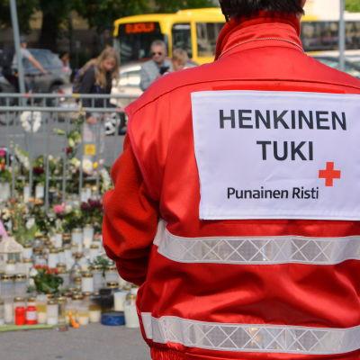 Person med röda korsets väst vid gravljus på Åbo torg.