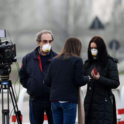 Reportrar med ansiktsmask i den lilla staden Casalpusterlengo, sydost om Milano 23.2.2020