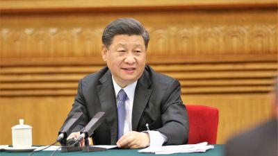 Presidentti Xi Jinping istuu pöydän takana ja puhuu mikrofoniin. Hänellä on edessään papereita. Presidentillä on tummanharmaa puku ja vaalenasininen kravatti.