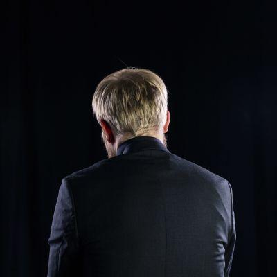 Pekka Vahvanen takaa päin kuvattuna mustassa studiossa.